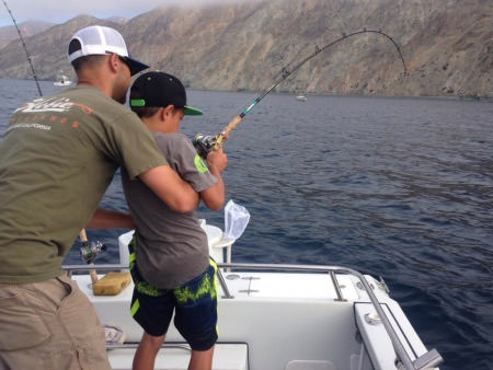 father helping son fish over the side of a boat