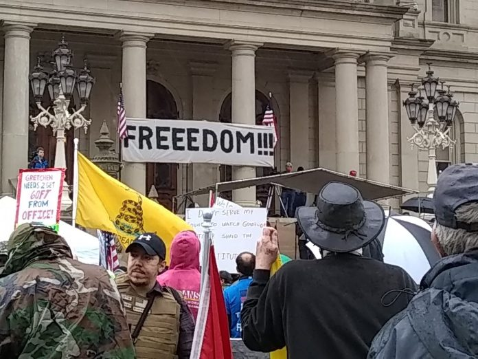 """People take part in a protest for Michiganders Against Excessive Quarantine at the Capitol in Lansing, Mich., on May 14,2020, """"Stand Up Michigan"""" sponsored this event. photo/video courtesy Bobby Powell, Michigan."""