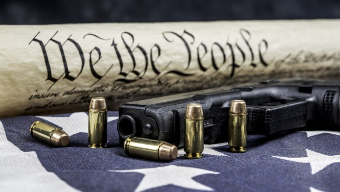 Constitution on an American Flag with a gun and bullets in the foreground