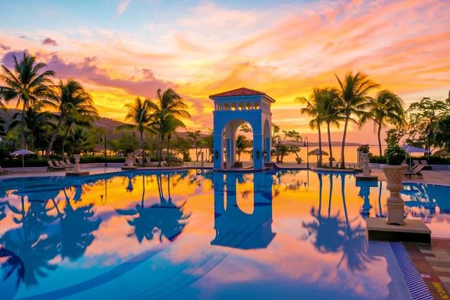 Palmiers et le lever du soleil se reflétant sur une piscine