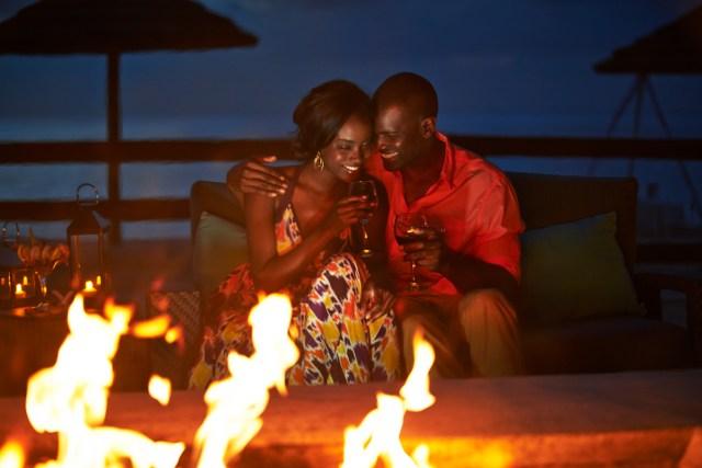 Un couple sirote du vin à côté d'un feu de camp