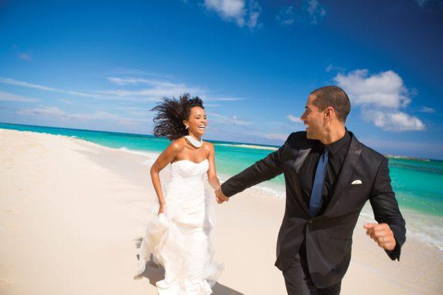 Jeunes mariés se tenant la main et courant le long de la plage de sable blanc