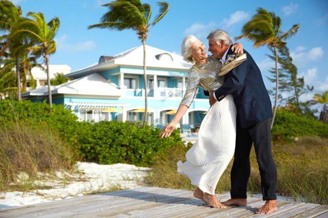 Un couple plus âgé fait une valse ludique sur une plage balayée par le vent.