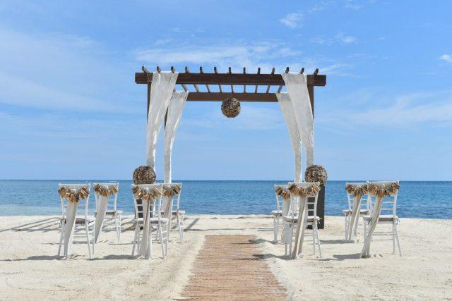 Des treillis en bois drapés de mousseline de soie et une gamme de chaises Chiavari blanches bordent une plage de sable blanc.