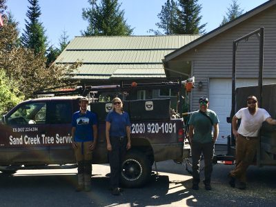 The Sand Creek Tree Service Crew stands next to the truck and trailer
