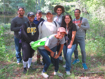 Dr. Conner Sandefur (third from left) and his undergraduate researchers (left to right): Anthony Arrington, K'Yana McLean, Nick Chavis, Tiffany Smart (kneeling), Desiree Cain, and Frederick Feely explore Sampson's Landing (in Pembroke) for medicinal plants. Joining the Sandefur lab for the day was Joshua Oxendine (in wide-brim hat).