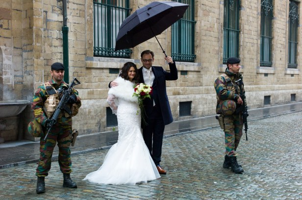 "Brussels Belgium 21 November 2015. Terror alert level for Brussels was put at 4, the maximum on a scale of 1 to 4. There is ""a very concrete and imminent threat"".These Greek-Flemish newly weds got married and have a portrait made with the military posing for their special marriage day. Bride Konstantina Karadimitropoulou and groom Roeland Lacroix holding umbrella"