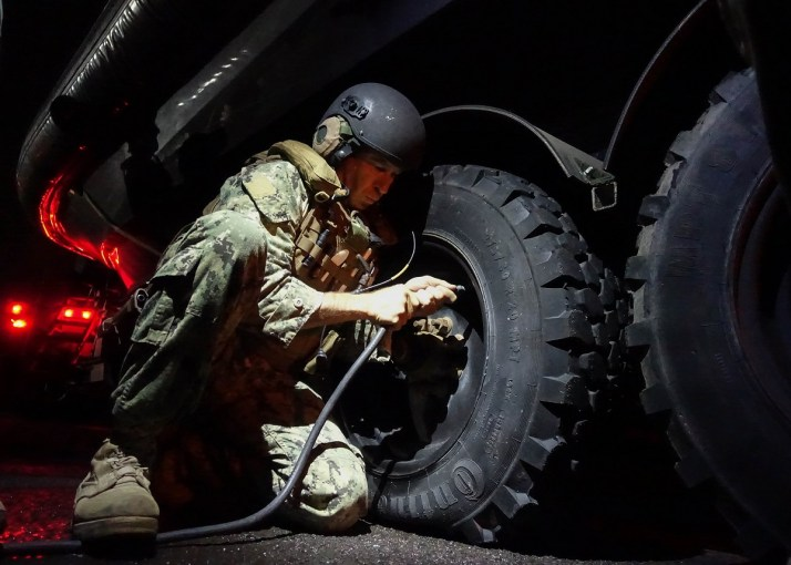 A Sailor works on inflating a tire