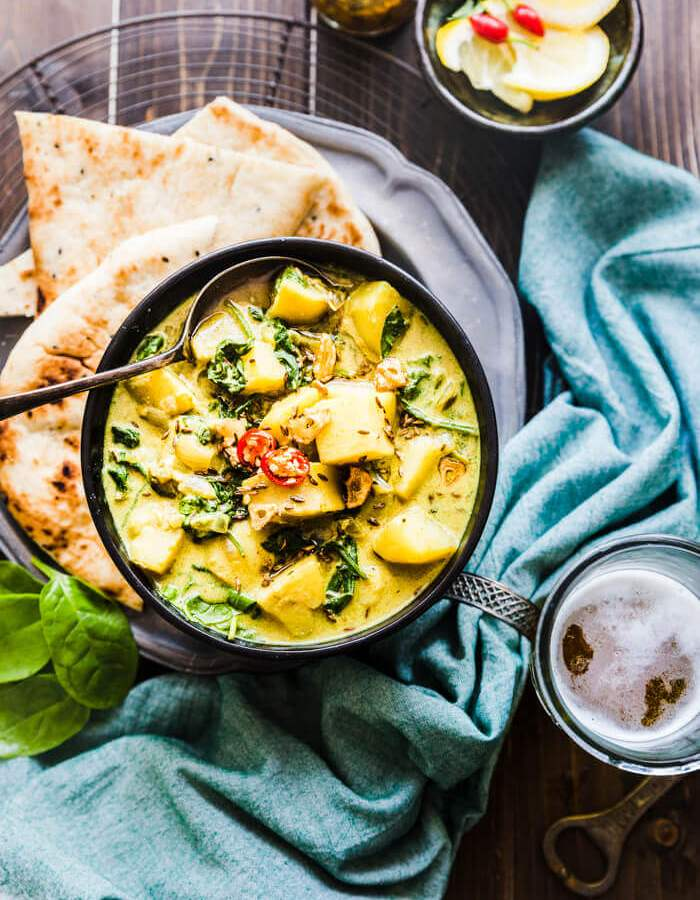 Saag Aloo served with naan bread and cider
