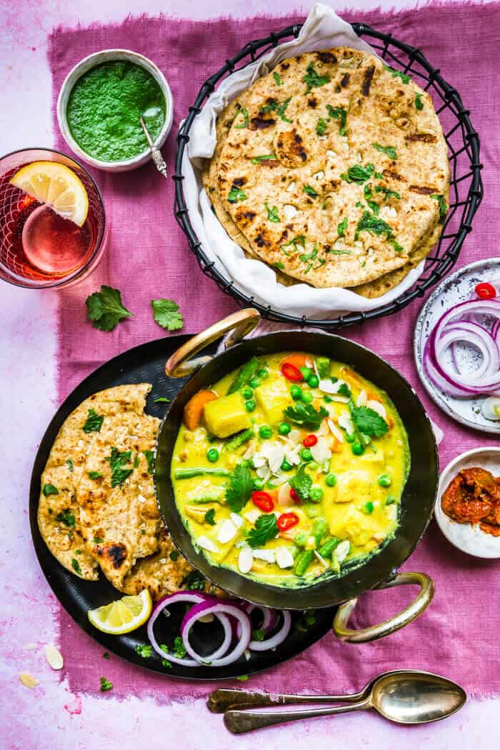 Vegan Korma served with roti on pink background