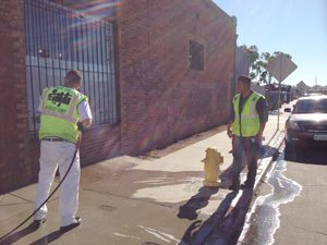 Urban Corps workers cleaning graffiti.