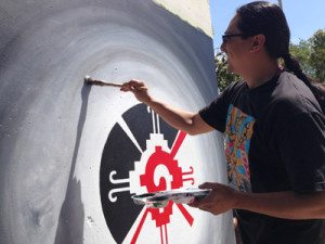 Artist and Barrio Logan resident Hector Villegas adds some blending to his mural.