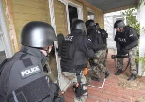 Police use a battering ram to force entry into the front door.