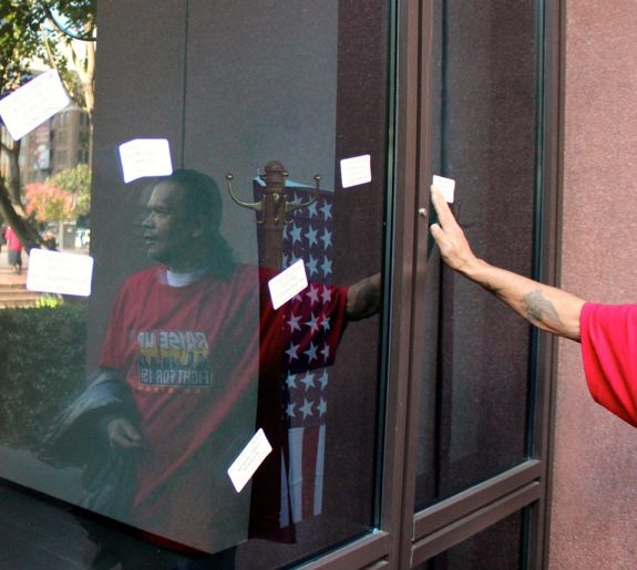 Protestors plastered the side of the Edward J. Schwartz Federal Building with stickers asking to end deportations, stop E-Verify and to give workers $15 and a union. (SEIU Photo)