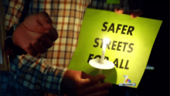 "BikeSD vigil participant holds ""Safer Streets For All"" sign"