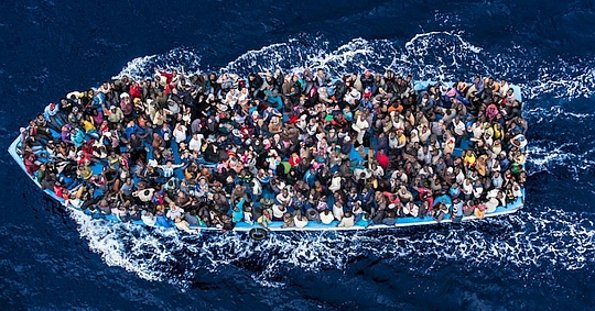 Refugees and migrants on a fishing boat pictured before making contact with the Italian navy.
