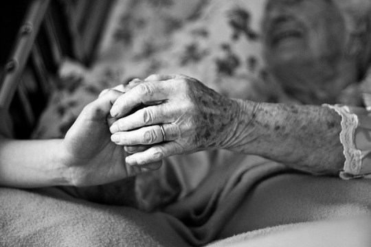 Elderly woman's hand holding a younger hand in her lap