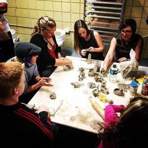 Group sitting around table working on ceramics