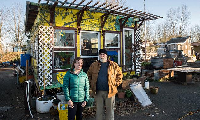 Katie Mays, the site's social worker, stands next to villager Rick Proudfoot in front of his house.Photo: Paul Dunn