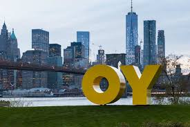 Large yellow sculpture work: the two letters O and Y in outdoor riverfront park with backdrop of New York skyline and bridge