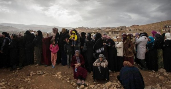 A line of female refugees from Syria waits to register with UNHCR in Arsal, Lebanon, November 2013. (Photo: M. Hofer/UNHCR/ Flickr. Some rights reserved.)