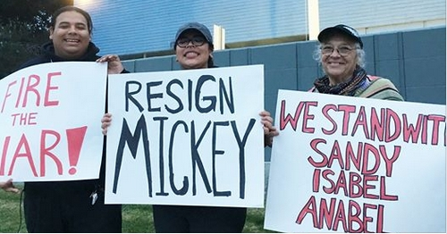 Three people holding signs protesting Mickey Kasparian