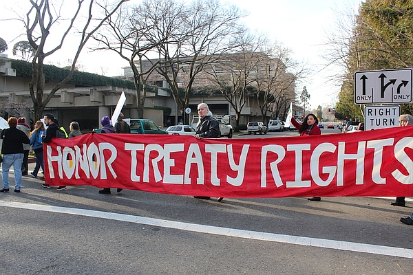 "Group in street holding banner reading ""Honor Treaty Rights"""