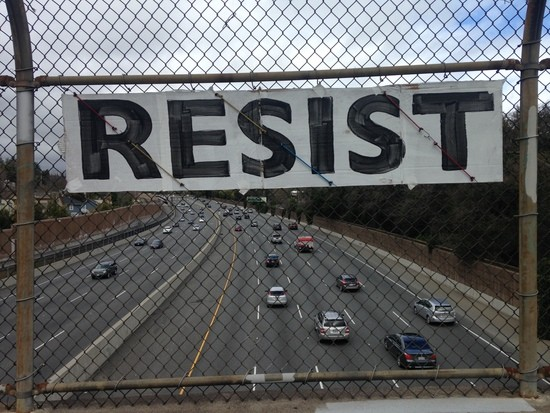 """RESIST"" banner on freeway overpass"