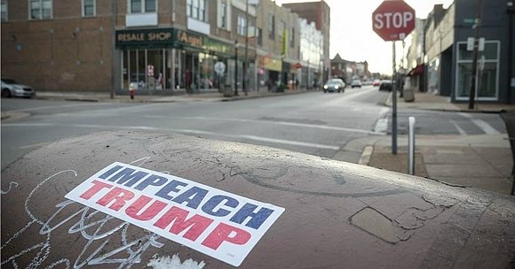 "Small town street intersection with ""Impeach Trump"" bumper sticker in foregound"