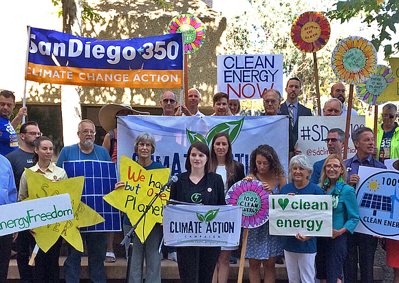 Group of people holding pro-environment signs flanking speaker at podium in outdoor setting