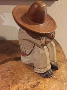 Carved wooden seated figure with sombrero