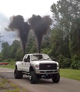 "A Ford F-450 monster truck stopped on a rural road ""rolling coal"", or blowing large clouds of dark grey diesel smoke."