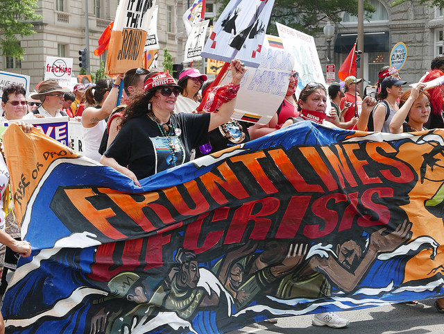 """Protest marchers carrying banner: """"Frontlines of Crisis"""""""