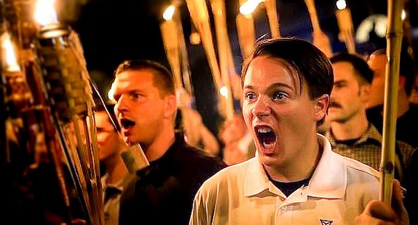 Group of young white men at night brandishing tiki torches and shouting