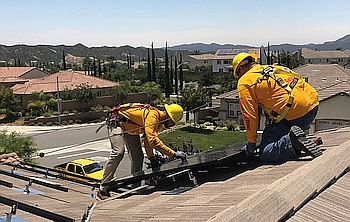 Construction workers installing solar panels on house roof