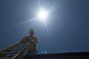 View looking up at construction worker on roof holding top of a ladder, full sun in sky