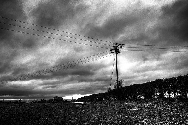 Black-and-white photo of landscape dominated by cloudy sky and lone telephone pole