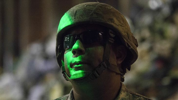 Head shot of helmeted soldier in green camouflage