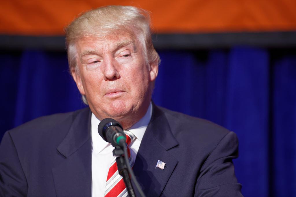 Trump speaking at microphone