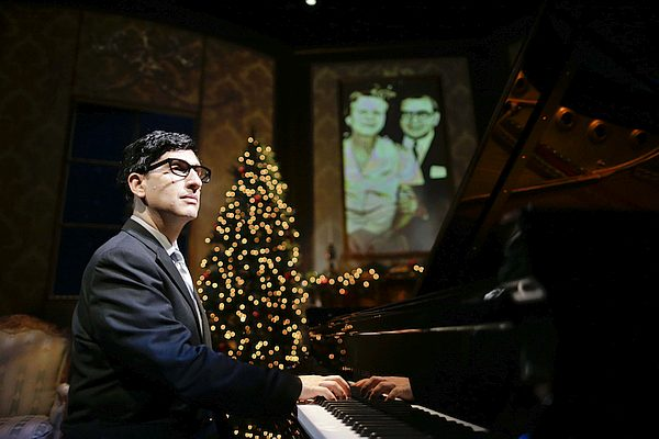 Man playing piano, Christmas tree in background