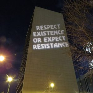 "Side of Denver, Colorado Federal Building with projected sign reading ""RESPECT EXISTENCE OR EXPECT RESISTANCE"""