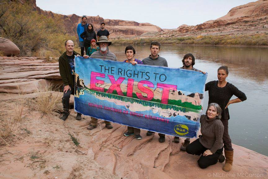 "Group on river bank holding banner reading ""THE RIGHT TO EXIST"""