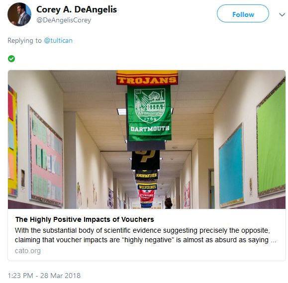Screenshot of a Tweet by Cory DeAngelis showing school hallway with college banners hanging from ceiling