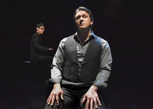 Stage scene, man playing piano, actor seated in front of piano