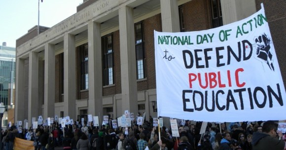 "Protest crowd with signs including one large one: ""NATIONAL DAY OF ACTION to DEFEND PUBLIC EDUCATION"""