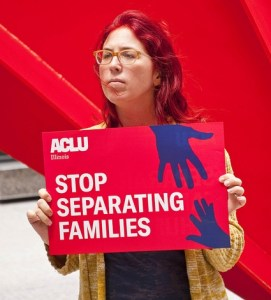 "Woman holding ACLU sign reading ""STOP SEPARATING FAMILIES"""