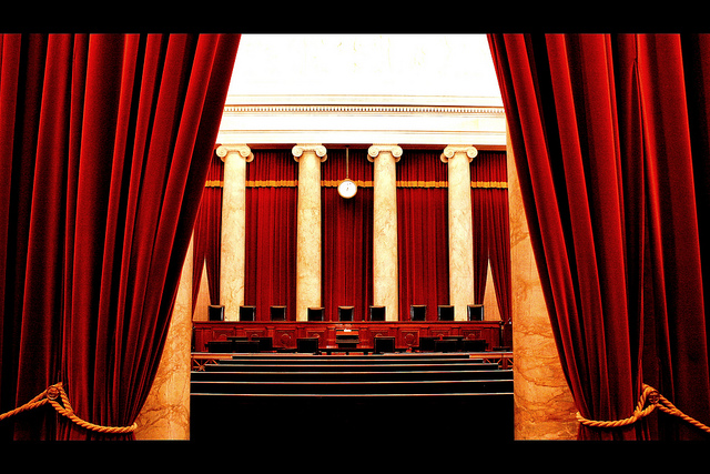 Interior of U.S. Supreme Court viewed between curtains as a stage setting
