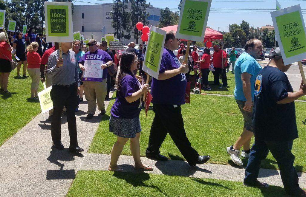 Protesters walking with signs supporting unions