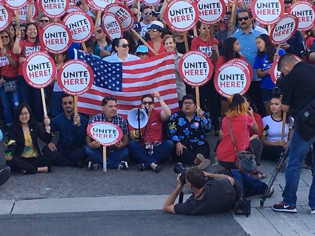 "Crowd of protesters holding flag and signs supporting unions saying ""UNITE HERE!"""