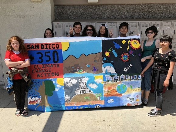 Group of teens holding up a climate themed mural